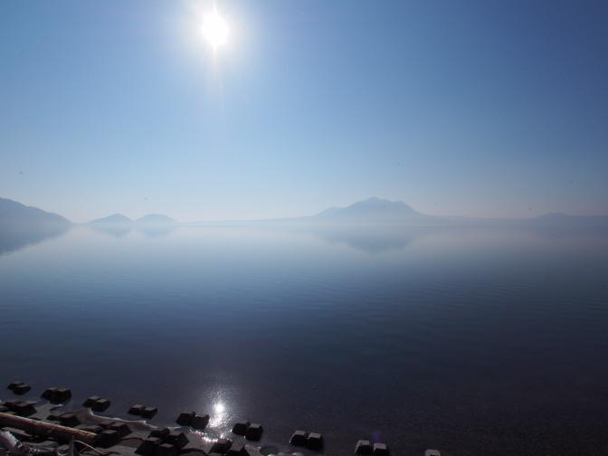 モヤがかかる中、湖面に対岸の山が写る幻想的な風景