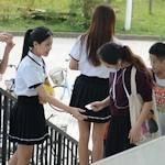 中国・福州大学で制服姿の女子大生が学生にコンドームを無料配布