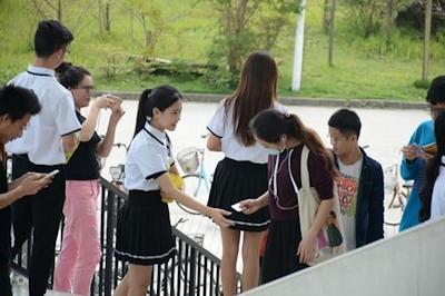 中国・福州大学で制服姿の女子大生が学生にコンドームを無料配布 1